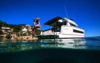 3 Personen springen von Badeplattform des Katamarans MY37 ins Meer