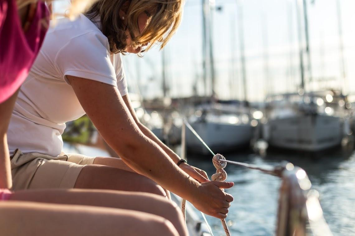 Frau befestigt Fender auf der Backbord seite von Segelboot